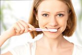 Happy woman brushing her teeth with a toothbrush — Stockfoto