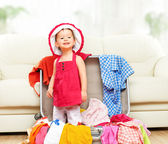 Happy baby girl is going on trip, pack suitcase — ストック写真