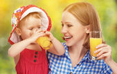 Family mother and baby daughter drinking orange juice in the sum — Stock Photo