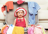 Happy baby girl is going on trip, pack suitcase — Stock Photo