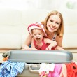 Mother and baby girl with suitcase and clothes ready for traveli — Stock Photo