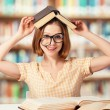 Tired funny girl student with glasses reading books — Stock Photo #44241131