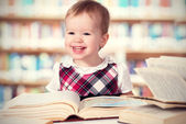 Happy baby girl reading a book in a library — Stock Photo