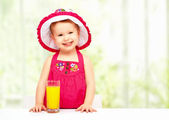 Baby girl drinking orange juice in the summer — Stock Photo