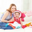 Happy Mother and baby girl with clothes ready for traveling on — Stock Photo #45406073