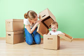 Happy family mother and baby daughter in an empty apartment with — Stock Photo