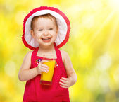 Baby girl drinking orange juice in the summer — Foto de Stock