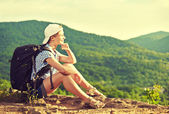 Woman tourist with a backpack sitting, resting on a mountain top — Stock fotografie