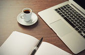 Work desk with a cup of coffee computer laptop, notebook, pen — Stock Photo