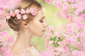 Young beautiful woman with pink flowers in her hair — Stock Photo