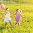 Happy twin sisters running around laughing and playing with balloons in summer — Stock Photo #50719655