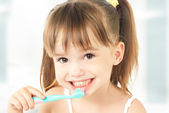 Happy little girl brushing her teeth — Stock Photo