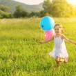 Happy cheerful girl playing and having fun with balloons in the summer — Stock Photo #51047109