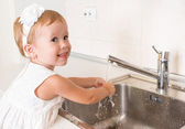 Baby girl washes her hands in the bathroom — ストック写真