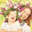 Happy laughing daughter hugging mother in wreaths of summer flowers — Stock Photo