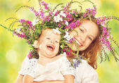 Happy laughing daughter hugging mother in wreaths of summer flowers — Stockfoto