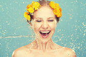 Beauty laughing girl with splashes of water and yellow flowers — Стоковое фото