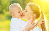 Happy family in summer. mother kissing her baby — Stock Photo
