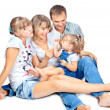 Positive family of four sitting and talking - Stock Photo