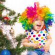 Cheerful girl in clown wig against the background of Christmas t - Stock Photo