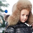 Boy in a warm hat on the background of the Christmas tree — Stock Photo
