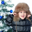 Royalty-Free Stock Photo: Boy in a warm hat on the background of the Christmas tree