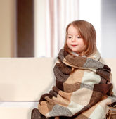 Girl dressed in a blanket sitting on the couch — Stock Photo