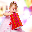 Portrait of the girl in the mall holding a gift - Stock Photo