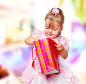 Portrait of the girl in the mall holding a gift — Stock Photo