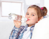 Portrait of a cheerful little girl drinking water from a bottle — Stock Photo