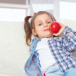 Little girl eating apples — Stock Photo
