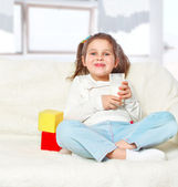 Beautiful girl drinking milk sitting on the couch — Stock Photo