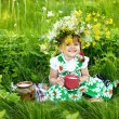 Baby girl is drinking milk sitting on a glade — Stock Photo #26556871