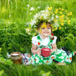 Baby girl is drinking milk sitting on a glade — Stock Photo
