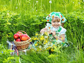 Baby girl is sitting on a glade and eating apples — Stock Photo