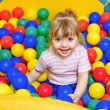 Little girl playing in the pool balls — Stock Photo