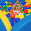 Stock Photo: Little girl playing in the pool balls