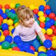 Little girl playing in the pool balls — Stock Photo #29607563