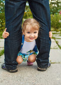 Little girl holding the feet of parents — Stock Photo