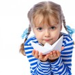 图库照片: Portrait of a little girl holding a paper boat on a white backgr