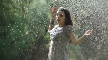 A beautiful girl begins to bustle on a lawn under a fountain — Stock Video