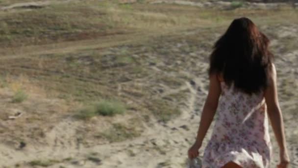 Chica se apresura hacia abajo en una montaña de arena — Vídeo de stock