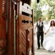 Groom and bride pass in a wooden gate — Stock Video #13626446