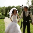 Groom and bride holding on to the hands, hurry on a path. — Stock Video