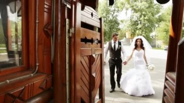 Groom and bride pass in a wooden gate — Stock Video