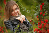 Beautiful girl near a positive snowball bushes. — Stock Photo