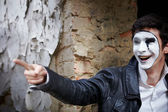 Guy mime against an old brick wall. — Stock Photo