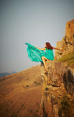 Girl sitting on the precipice of a cliff. — Stock Photo