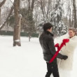 Stock Video: Newlyweds play with red scarf in snowy winter park.