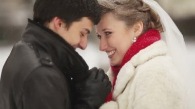 Newlyweds warm to each other in a snowy winter park — Stock Video